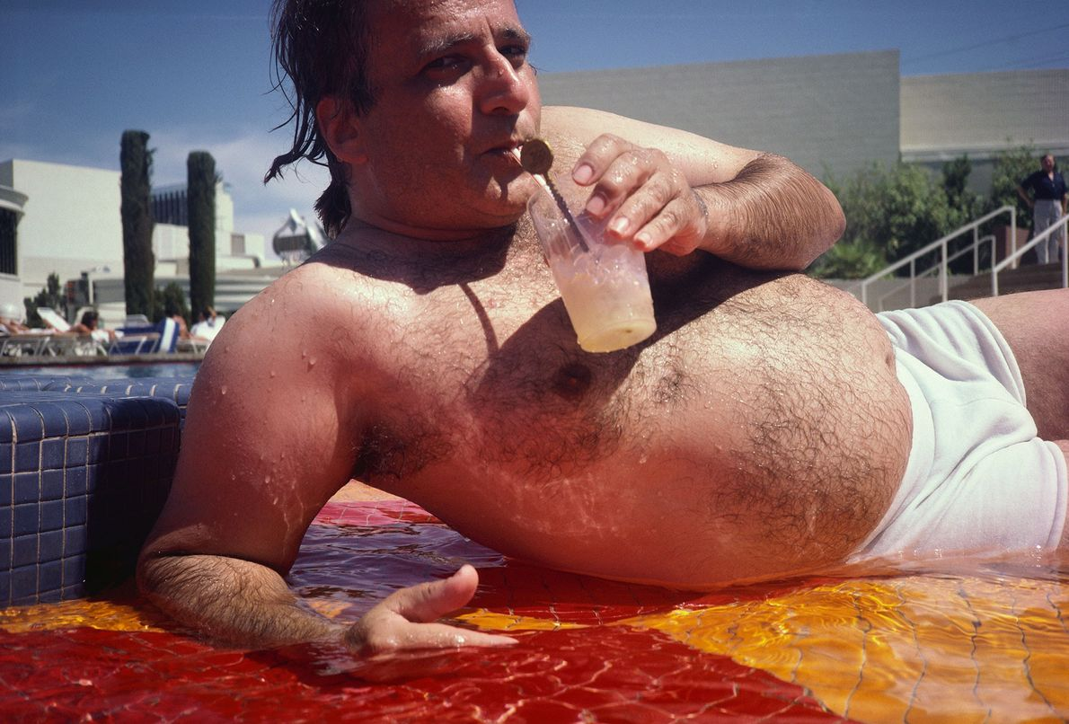 A swimmer sips his drink while lying in the shallows of a pool at Caesar's Palace ...