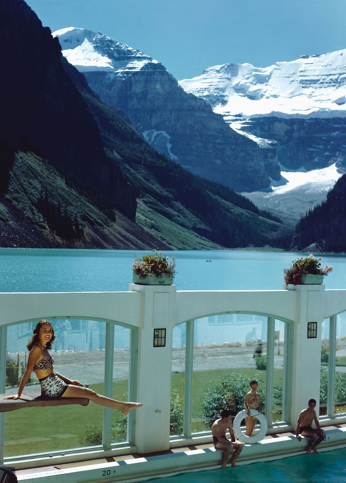 Visitors swim in a pool with a stunning view of the nearby mountains at Chateau Lake ...
