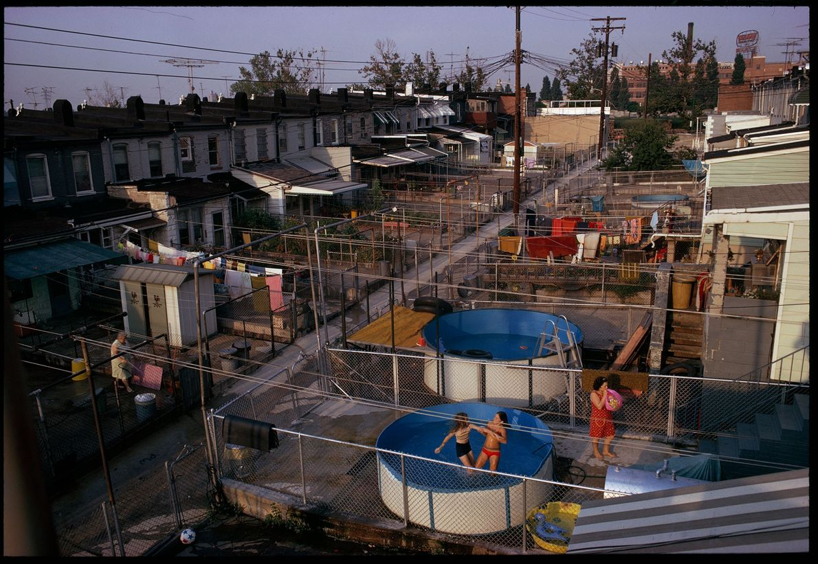 Small backyards with large above-ground swimming pools serve as summer playgrounds in East Baltimore, Maryland.