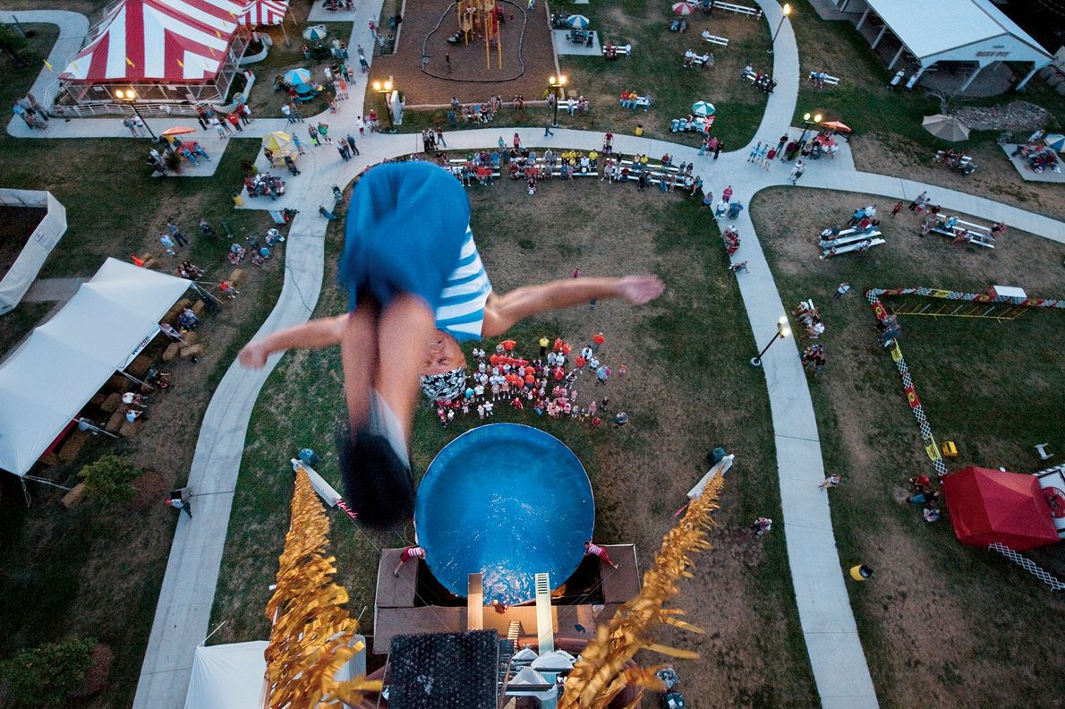 """A diver plunges from a platform atop an 80-foot tower during the high-dive act """"Pirates of ..."""