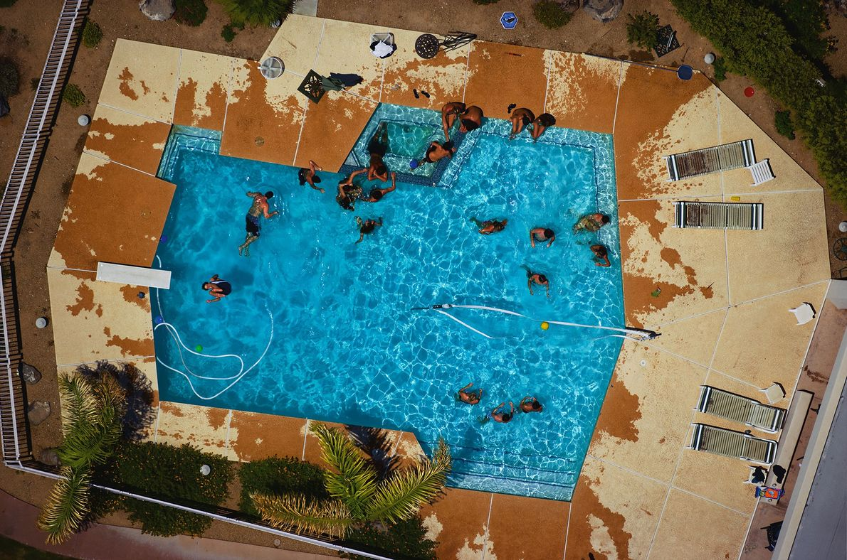 People relax in a backyard swimming pool at a home in Phoenix, Arizona.