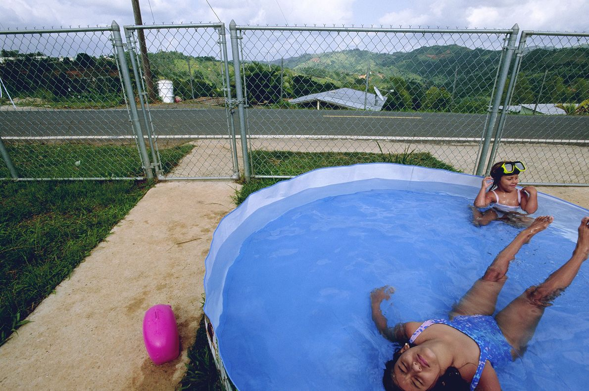 Two sisters keep cool in their front-yard pool in Corozal, a region close to San Juan, ...
