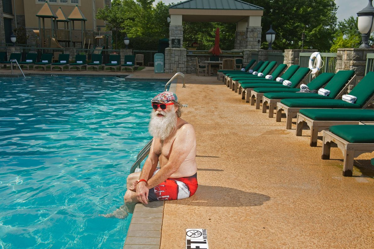A professional Santa Claus tans and swims by the pool at Chateau by the Lake Resort ...