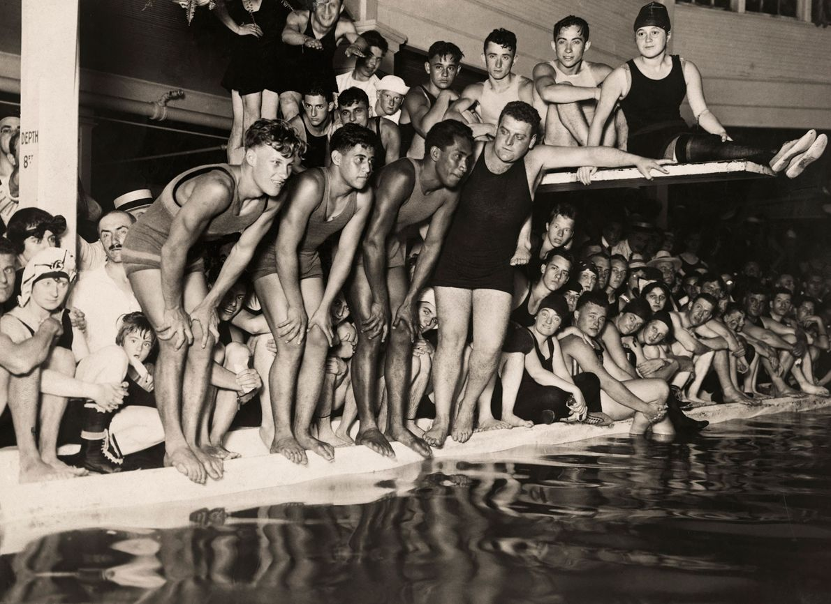 Three competitive swimmers in the early 1900s prepare to race against one another in Hawaii.  ...