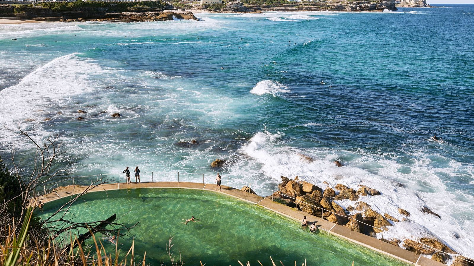 Overlooking bathers beside the green Bronte Ocean Pool, next to the blue ocean and crashing waves.