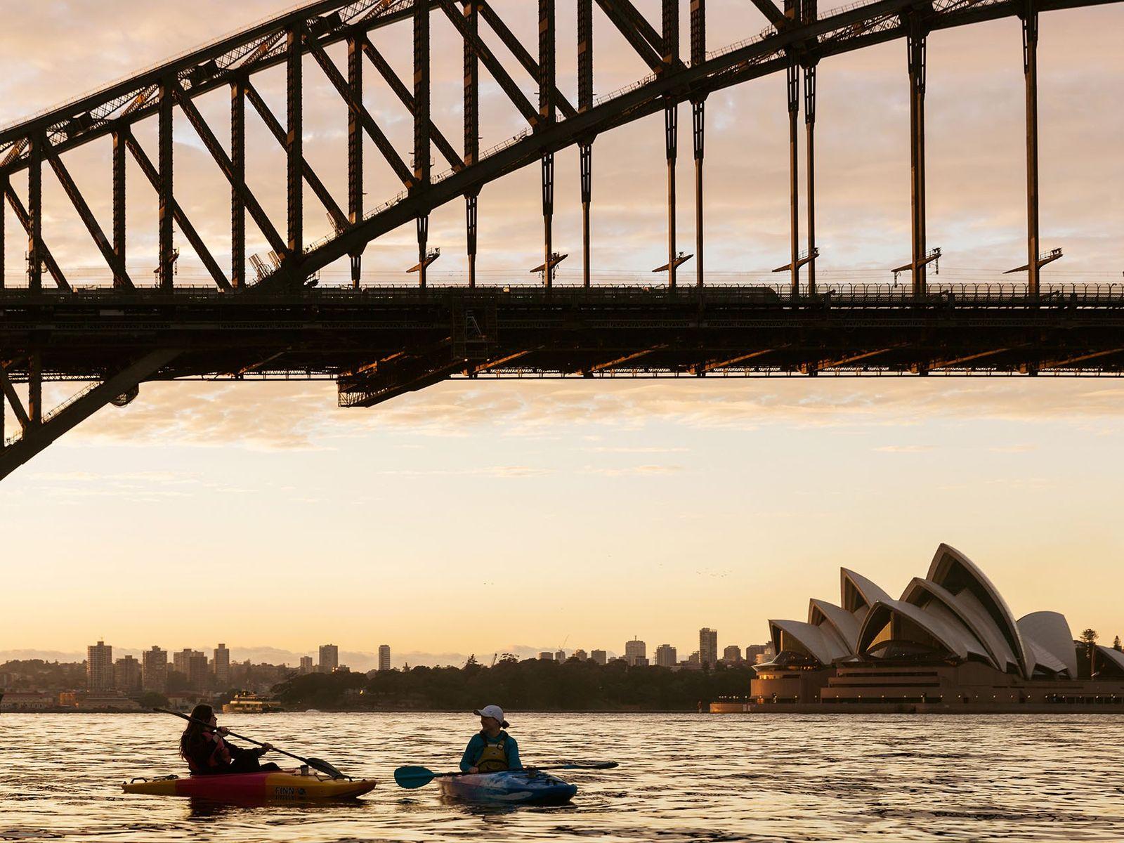 Kayakers under the Sydney Harbour Bridge at sunrise