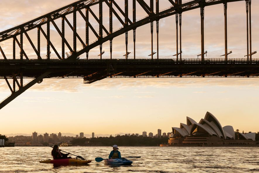Kayakers at sunrise under the Sydney Harbour Bridge.