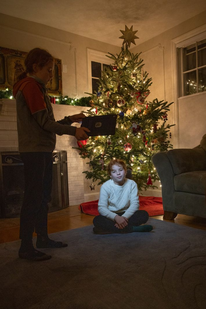 Hale's son shines the light from a tablet onto her daughter, posing in front of the ...