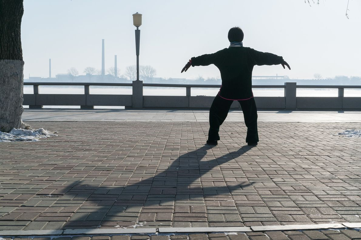 A woman practices tai chi in freezing temperatures near the Yalu River in Dandong, China, which ...