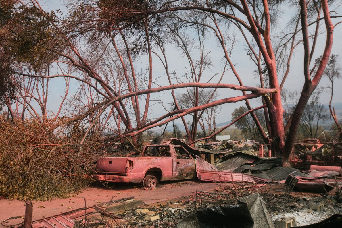 A burnt pickup truck, covered by fire retardant, lies among the remains of Oregon's Talent Mobile ...