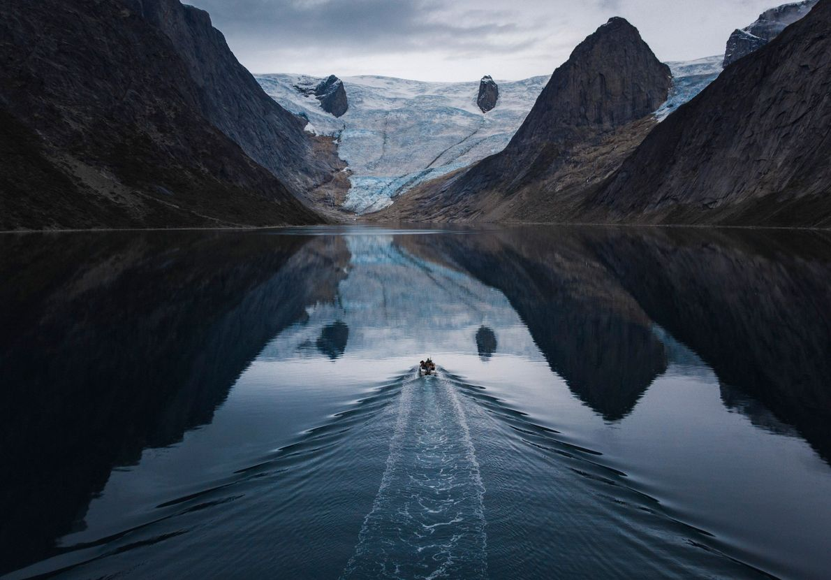 A local fisherman boats near Tasermiut Fjord. Chu connected with local boaters to transport him to ...