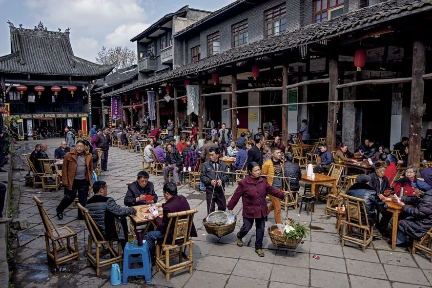 Teahouses enliven a street in Luocheng, Sichuan, where customers play cards or chess, trade stories, and ...