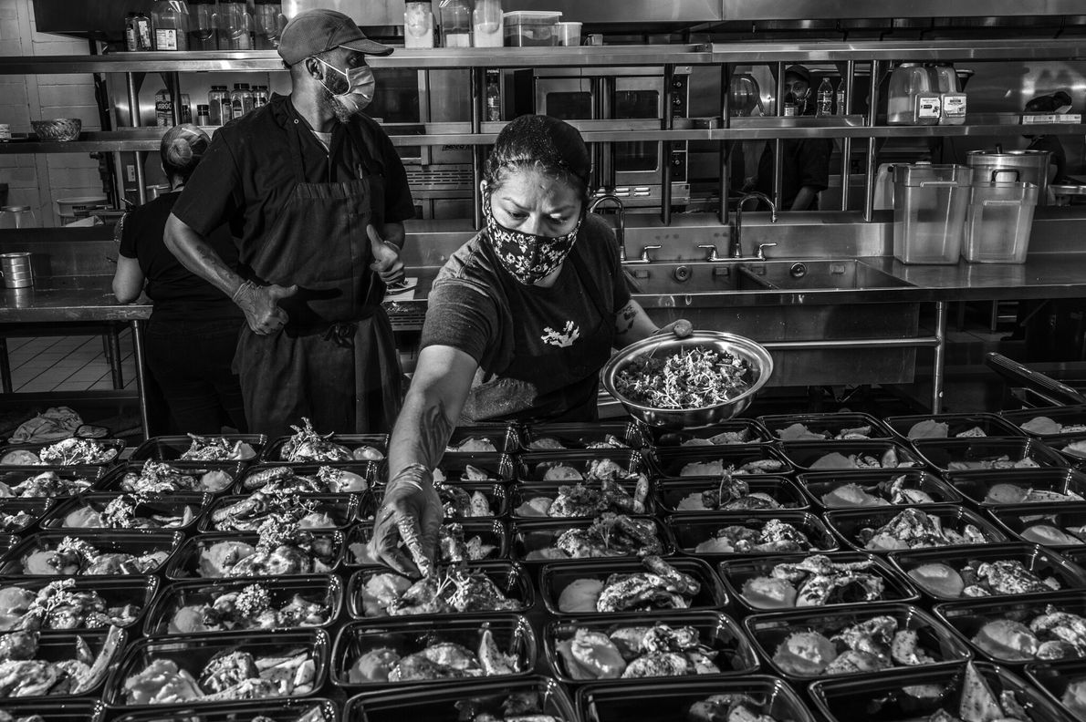 Staff at Lucille's 1913, a non-profit pop-up kitchen run by owner Chris Williams, prepare free meals ...