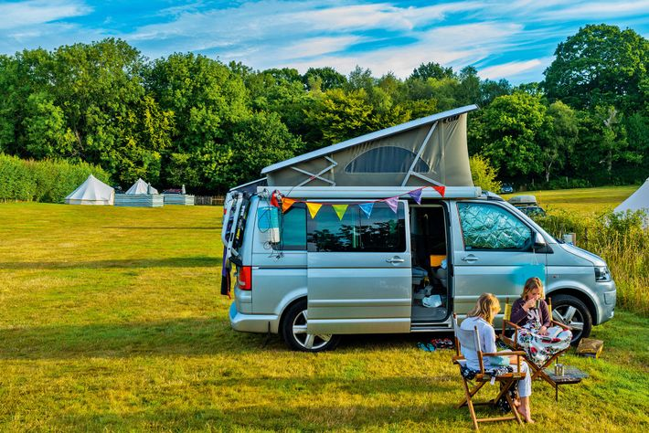 A family goes camping in a field in East Sussex. Around80% of a holiday's carbon footprint ...