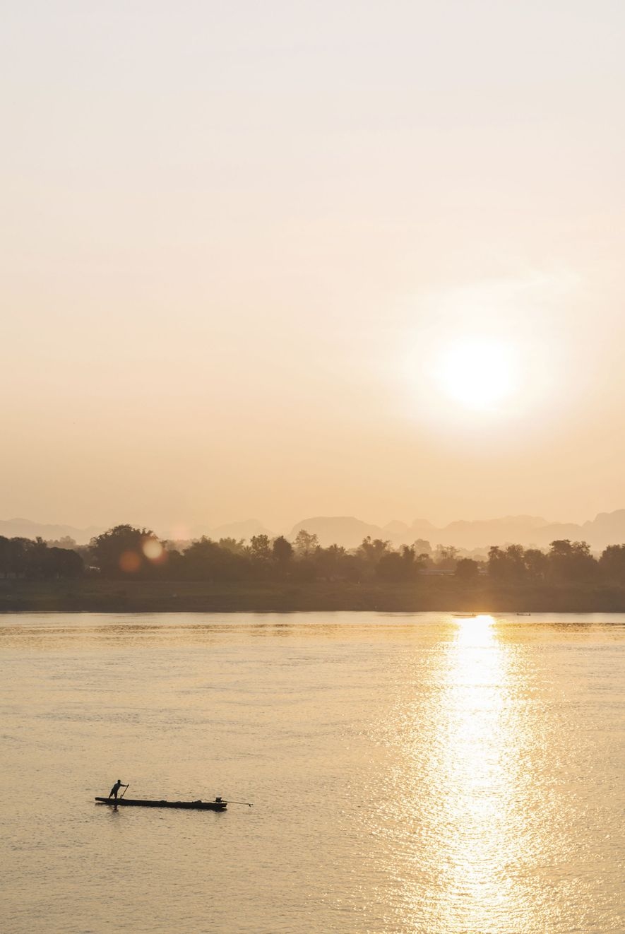 As the sun begins to rise, a fisherman plies the waters of the Mekong near Nakhon Phanom