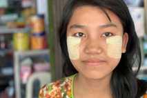 Mi Mi Shaw, 16, staffs an electronics shop in Shwebo, Myanmar, wearing a daily coat of ...