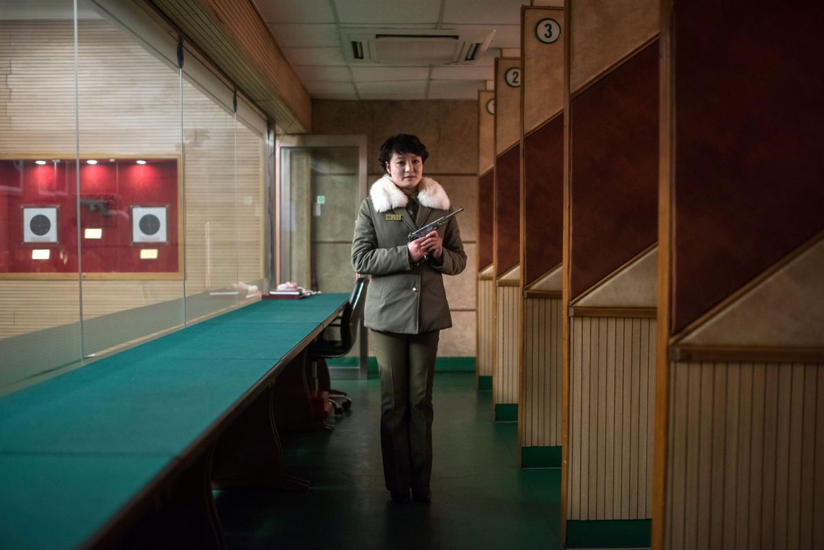 North Korean shooting instructor Kim Su Ryon holds a gun and poses for a portrait at ...