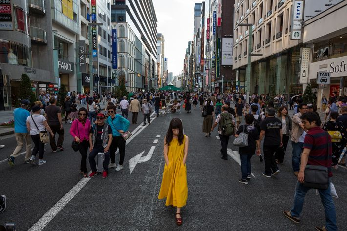 Pedestrians, shoppers, and people-watchers stroll on Chuo-dori in Ginza, one of Tokyo's busiest destinations. Cars travel ...