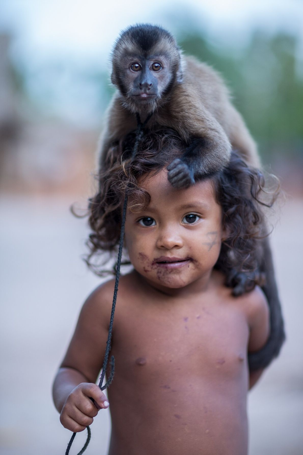 Gazielly poses with her family's pet Guianan brown capuchin. She lives in the Awá community that ...