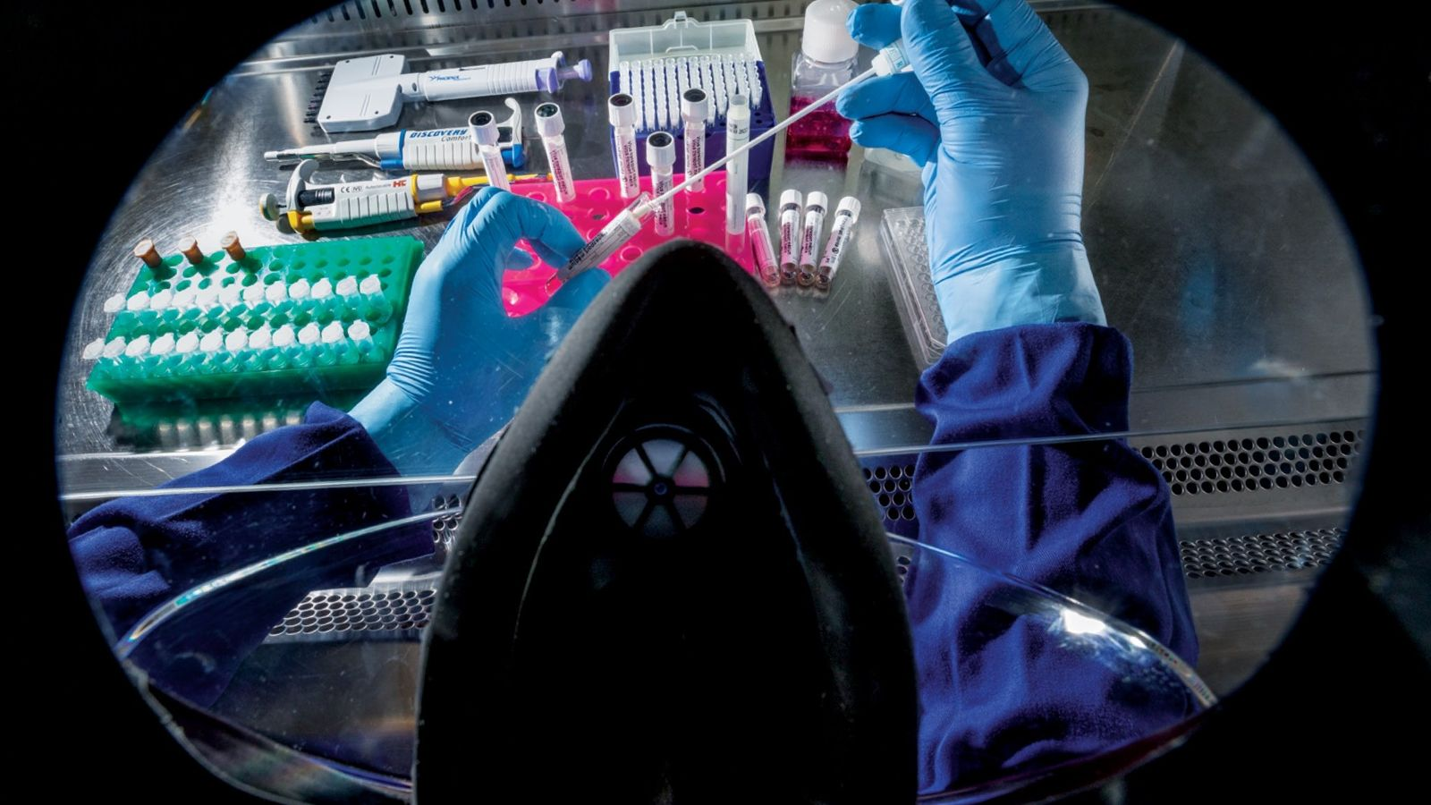 This laboratory work space is photographed through a technician's face shield and past its respirator mask ...