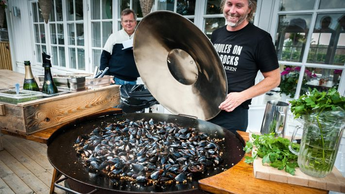 Fisherman host Janne Bark cooking mussels on the decked terrace of his Mussel Bar.