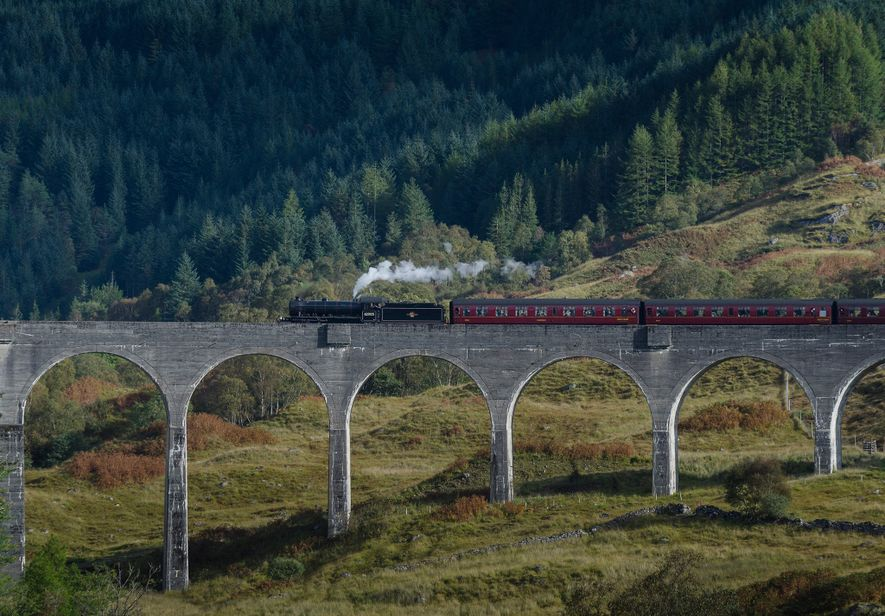 Train travellers cross the Glenfinnan Viaduct in Scotland.