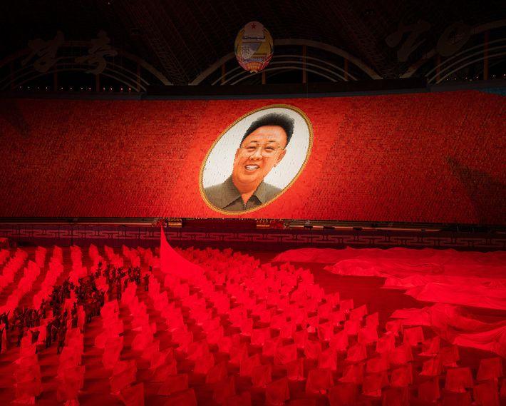 A massive portrait of Kim Jong-il, the second Supreme Leader of North Korea, hangs over the ...