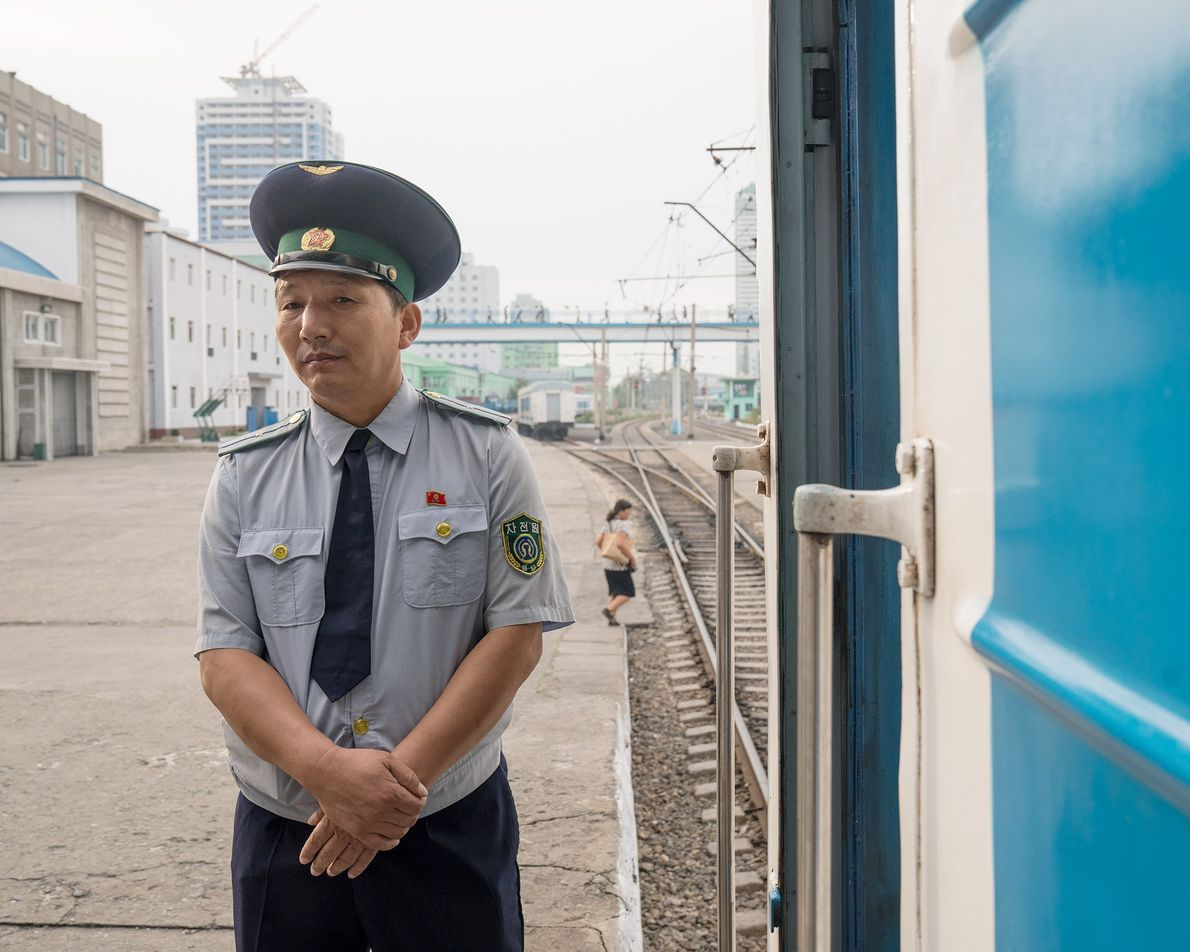 A rail worker stands on the platform at the Pyongyang train station.