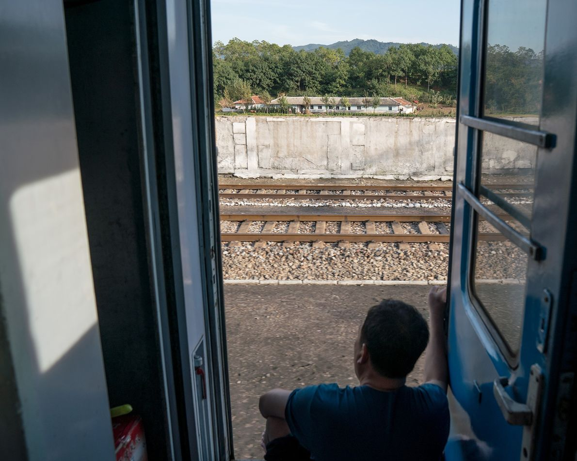A passenger gazes out at the landscape on the way from Pyongyang to Rason.