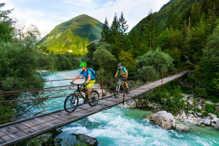 Cyclists cross a bridge in Slovenia's Soča valley.