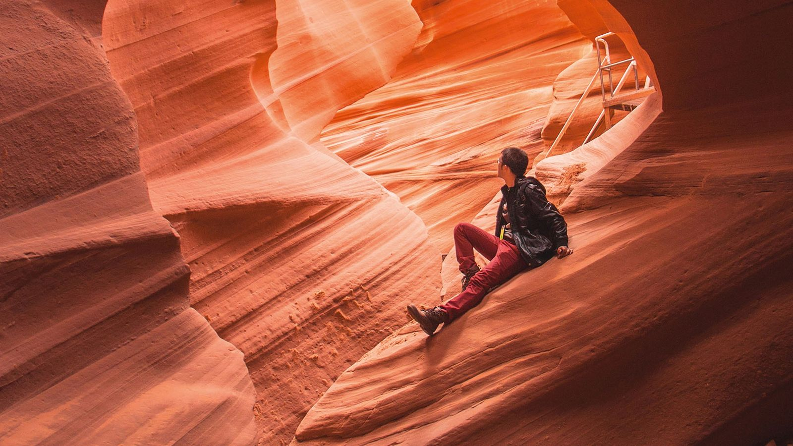 Man sitting on rock in Antelope Canyon