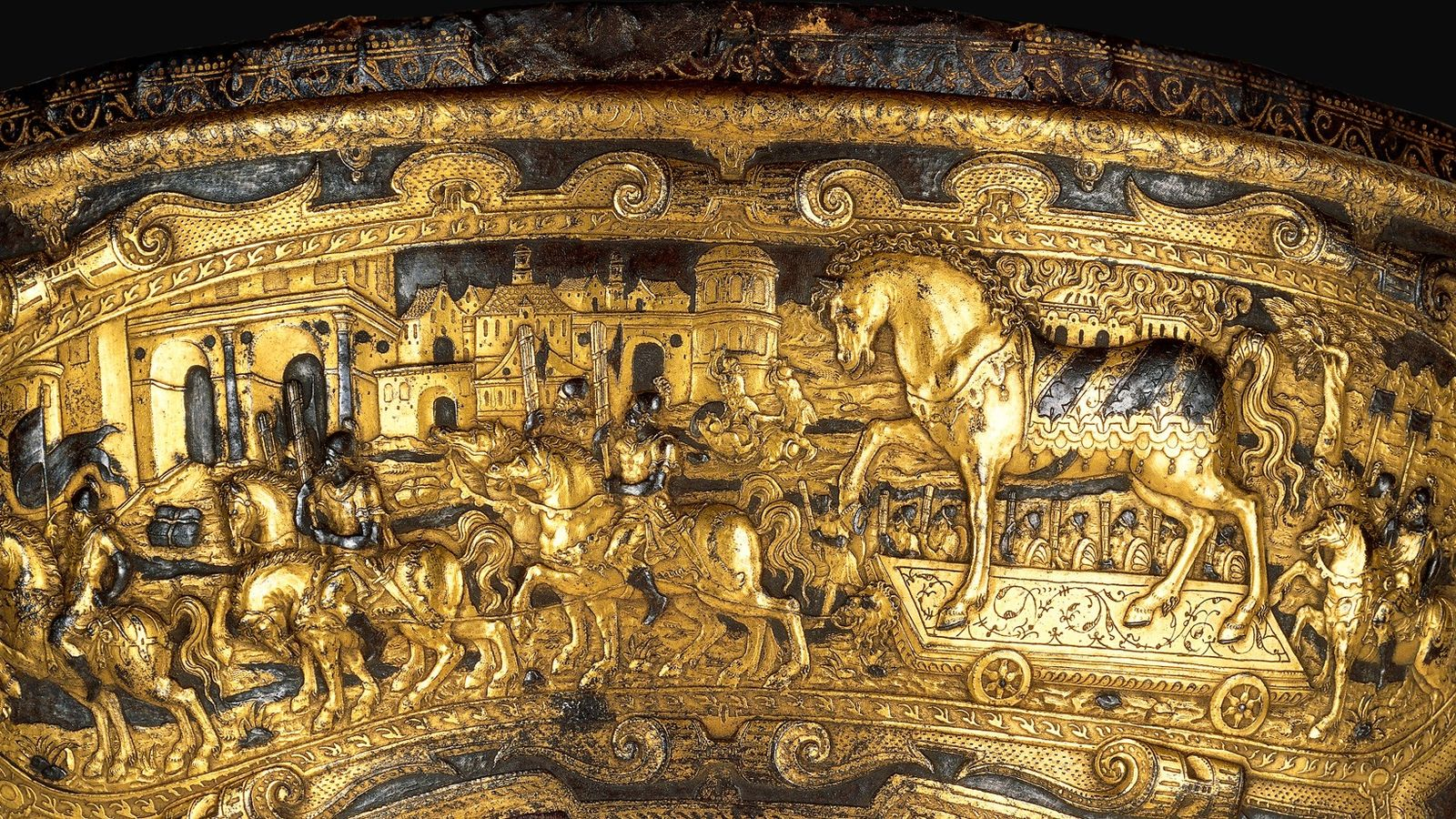This magnificent 16th-century saddle shows the Trojans bringing the wooden horse into their city, unaware of ...