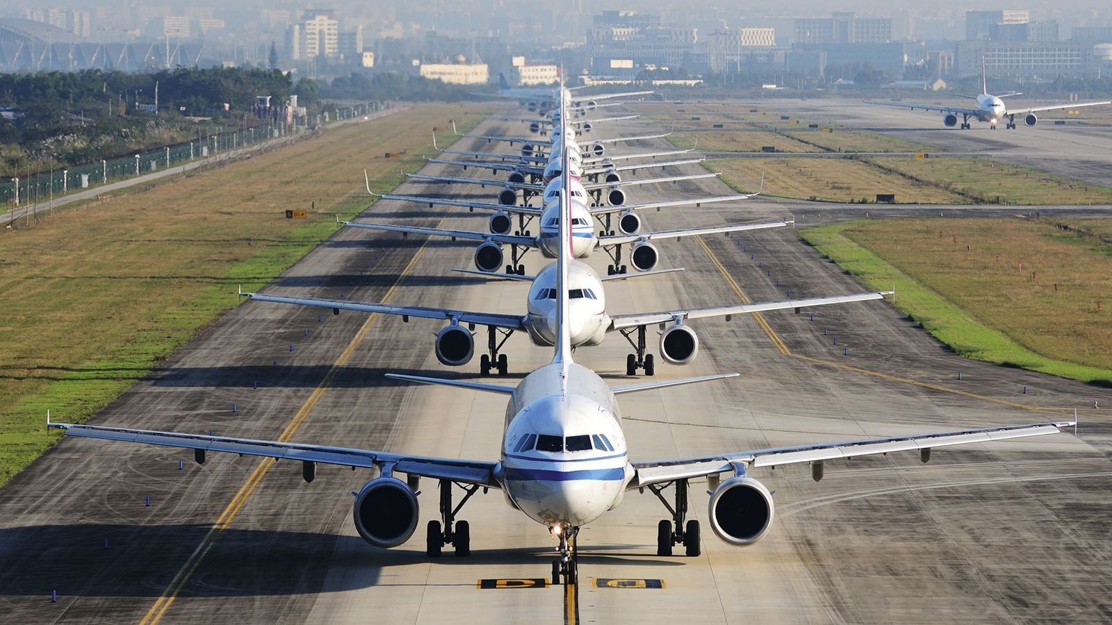 A queue of airplanes on a runway