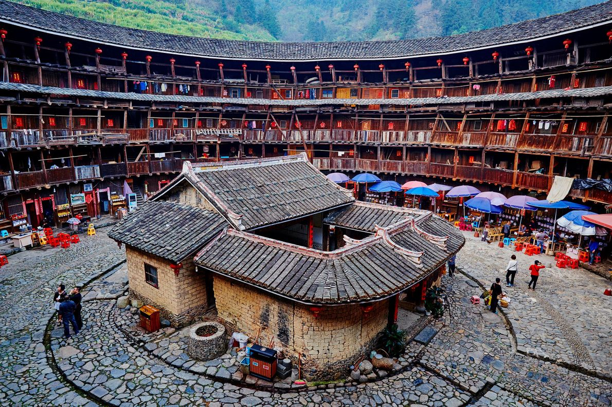 "Southeastern China hosts more than 40 tulous—circular housing complexes, also called ""earthen houses""—that sit among rice, …"