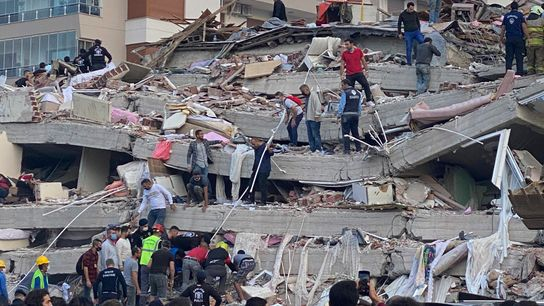 Rescue workers and locals search for residents trapped in the debris of a collapsed building in ...