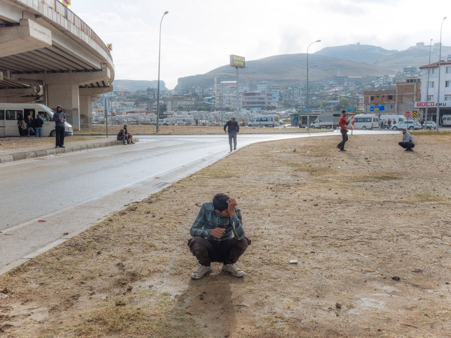 "Adult concerns on a child's shoulders: Khalil, 16, waits and hopes for work as a day labourer in Hatay. He has been coming to this spot, along with other young would-be refugee workers, every morning since he was 11. ""We rarely get a job,"" he says. ""We mostly wait for nothing."""