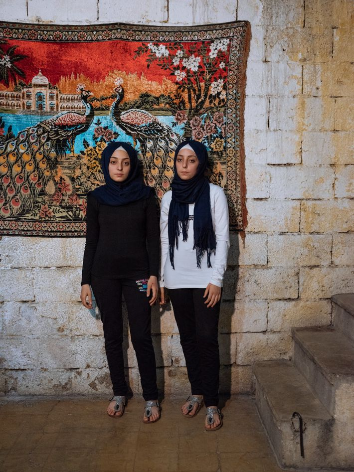 """Fourteen-year-old twins Sidra (at left) and Shahed remember the barrel bombs in Aleppo that forced them ..."