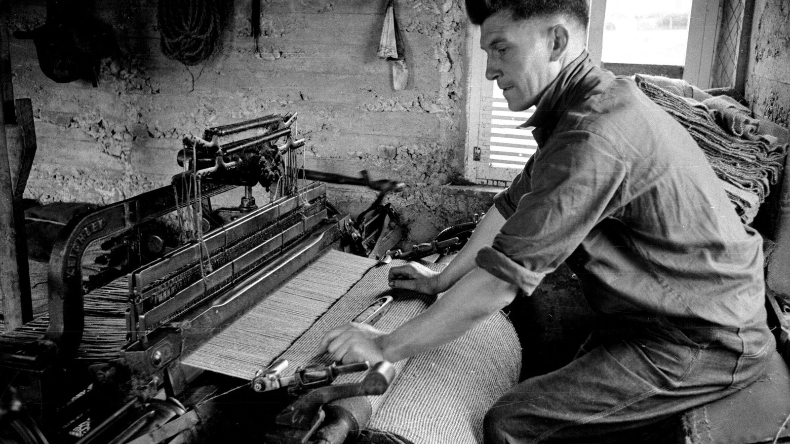 In this 1955 photo, a weaver in the Outer Hebrides is shown producing Harris Tweed on ...