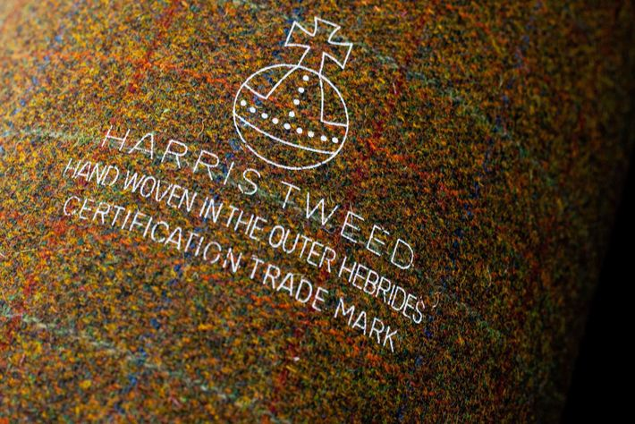 A bolt of Harris Tweed gets stamped with an orb trademark to designate its origin in ...
