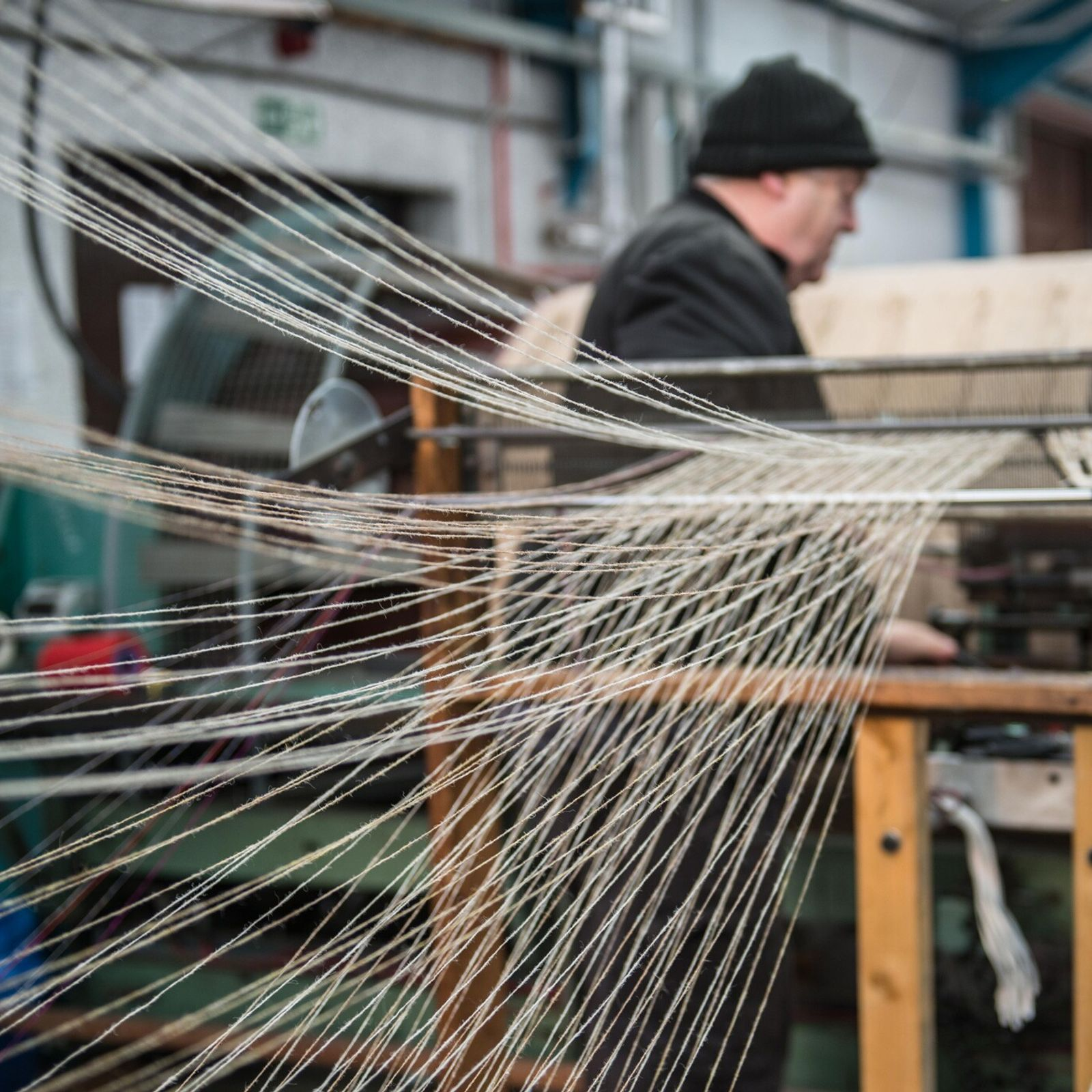 A worker in the Outer Hebrides produces tweed on an outsized loom.