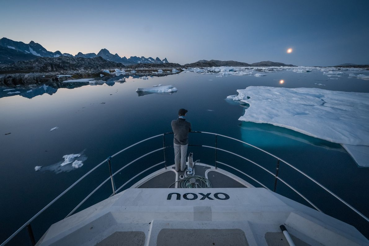 Libecki keeps watch as his boat manoeuvres around icebergs in the Greenland Sea at dusk.