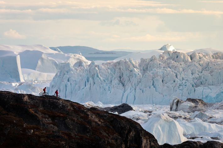 Two bikers at Ilulissat Icefjord. There are various ways to see the icebergs of Greenland — ...