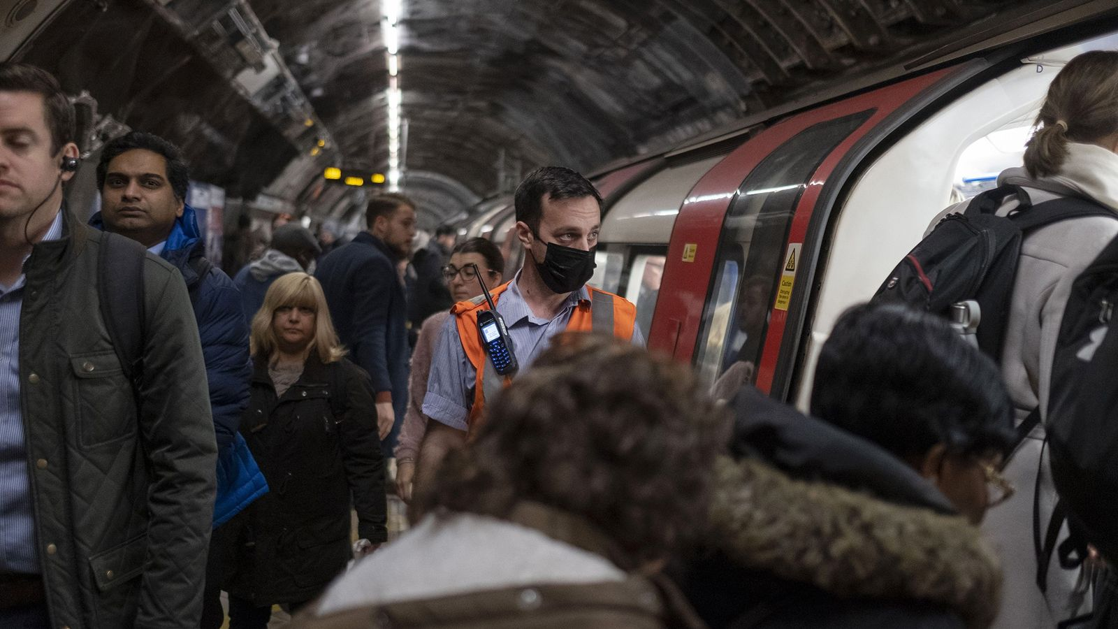 A staff member from the London Underground wears a protective face mask while passengers board the ...