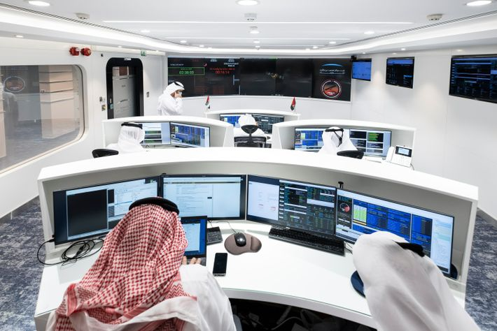 Scientists and technicians monitor progress from mission control.