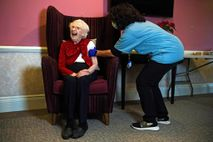 Hundred-year-old Ellen Prosser, known as Nell, receives the Oxford-AstraZeneca COVID-19 vaccine at the Sunrise Care Home ...