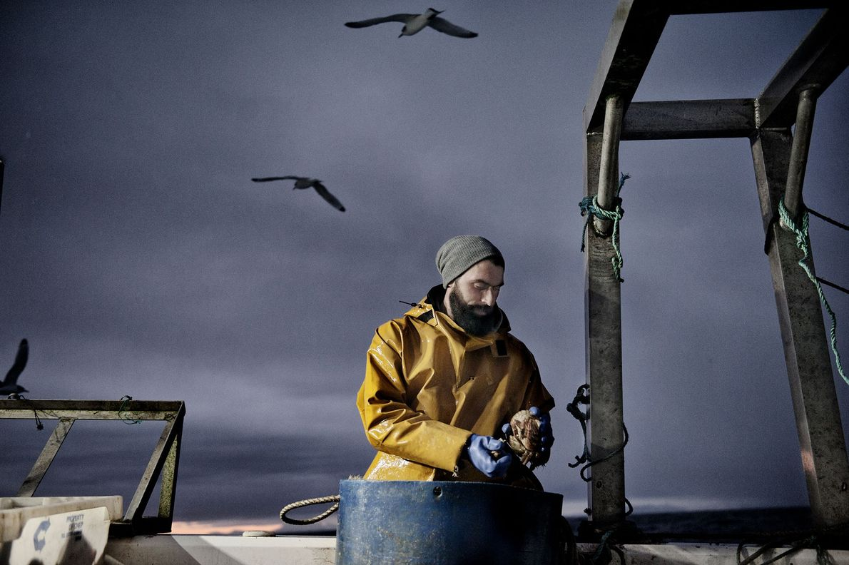 Kevin, 35, works as a fisherman. He is photographed off the Isle of Lewis.