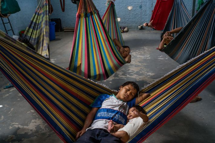 Hammocks provide traditional sleeping arrangements over the concrete floor at Pacaraima's Janokoida shelter. These two brothers ...