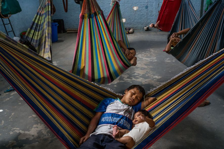 Hammocks provide traditional sleeping arrangements over the concrete floor at Pacaraima's Janokoida shelter. These two brothers have lived there for several months.