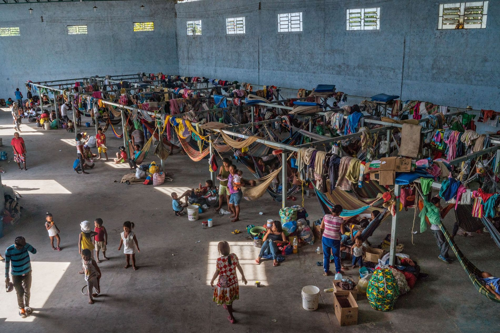 About 500 members of the Warao tribe live at a concrete shelter outfitted with hammocks and tents in Pacaraima, Brazil. Crowding and unsanitary conditions have contributed to widespread disease.