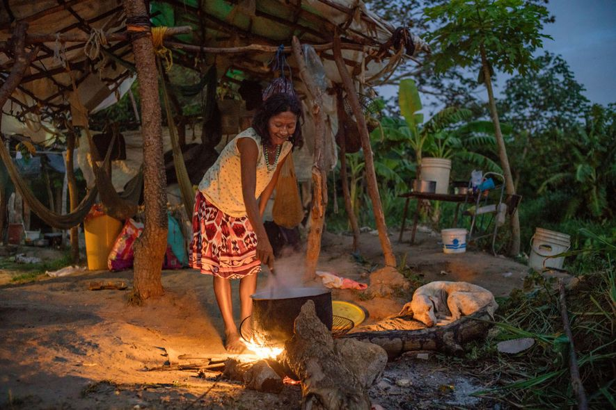 A Warao woman cooks dinner over a campfire near Ciudad Guayana, Venezuela, on the way to the Brazilian border. Many Warao walk or hitchhike to shelters in Brazil, a journey that can take days.